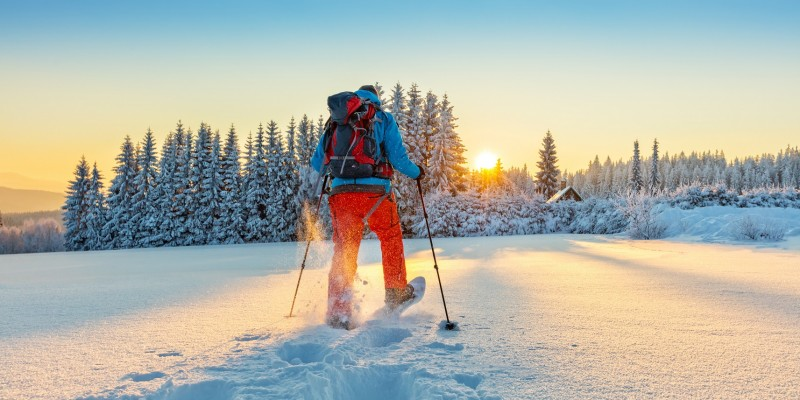 Snowshoe walker running in powder snow with beautiful sunrise light. Outdoor winter activity and healthy lifestyle