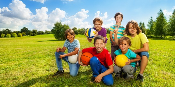 Group of six boys, team sitting on the grass with balls happy and smiling, on sunny summer day