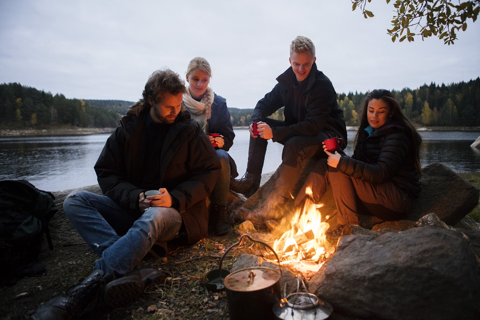Multiethnic friends with coffee cups sitting near campfire on lakeshore
