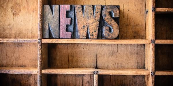 The word NEWS written in vintage wooden letterpress type in a wooden type drawer.