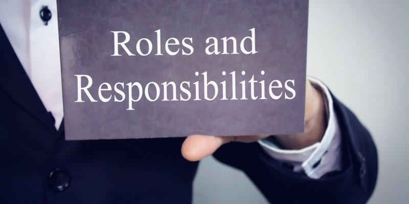 Roles and Responsibilities - Businessman holding chalkboard with text.