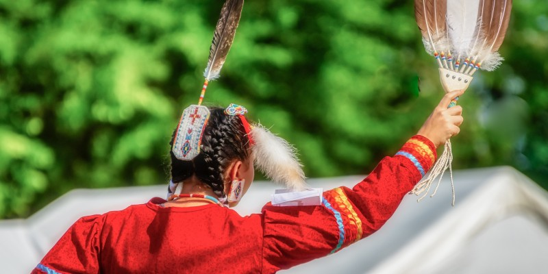 A closeup shot of the head of a person in a traditional Native Indian-American festive hat with feathers
