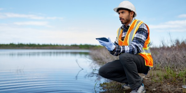 Portait of a professional scientist with protective gear examining the marsh lands in Canada and taking sample reading on a digital tablet